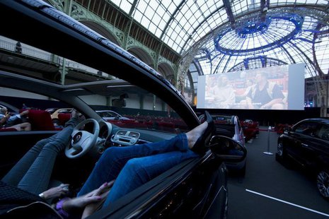 Visitors watch a film as they attend the opening night of a drive-in cinema, which will run till June 21, at the Grand Palais in Paris June