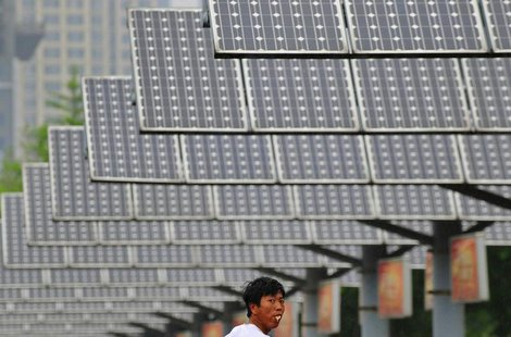 A man eats his breakfast as he walks under solar panels belonging to a solar power plant in Shenyang, Liaoning province June 5, 2013. REUTER