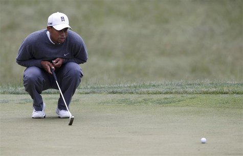 Tiger Woods of the U.S. looks at his birdie putt on the 13th green during completion of the weather delayed first round of the 2013 U.S. Ope