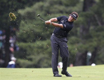 Phil Mickelson of the U.S. makes his second shot on the first hole during the first round of the 2013 U.S. Open golf championship at the Mer