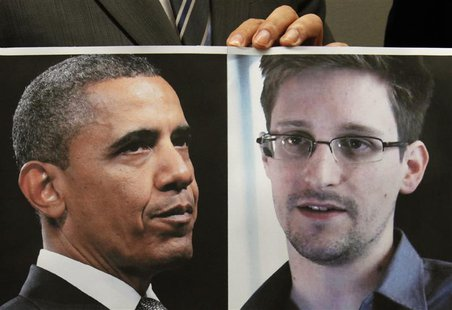 Pro-democracy lawamaker Gary Fan holds a combination photo featuring U.S. President Barack Obama (L) and Edward Snowden, a contractor at the