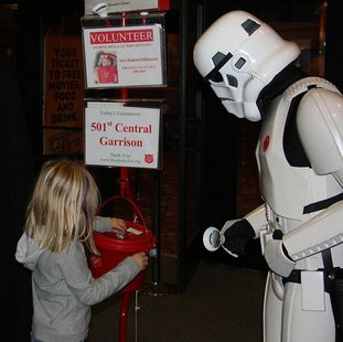 A volunteer dressed as a Star Wars Imperial Stormtrooper ringing a bell to solicit donations for the Salvation Army as a young girl places money in the red kettle at a movie theatre in Rochester, Minnesota By Jonathunder (Own work) [GFDL 1.2 (http://www.gnu.org/licenses/old-licenses/fdl-1.2.html)], via Wikimedia Commons