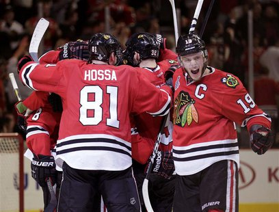 Chicago Blackhawks center Jonathan Toews (19) celebrates with his team after they defeated the Boston Bruins in triple-overtime in Game 1 of