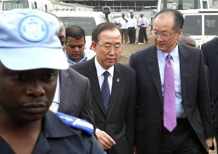 A U.N. peacekeeper escorts U.N. Secretary-General Ban Ki-moon and World Bank President Jim Yong Kim (R) during their joint trip to Goma, in