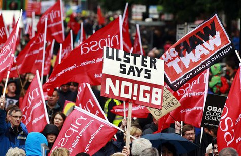 Protesters wave placards and flags during an anti-G8 demonstration ahead of the summit, at Belfast City Centre June 15, 2013. REUTERS/Cathal