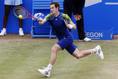 Britain's Andy Murray hits a return to France's Jo-Wilfried Tsonga during their men's singles semi-final tennis match at the Queen's Club Ch