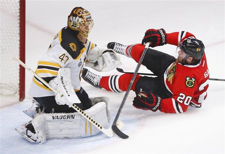 Chicago Blackhawks' Brandon Saad (R) slides into the net behind Boston Bruins goalie Tuukka Rask during the sceond period in Game 2 of their