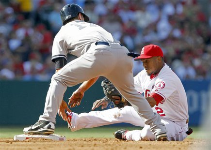 Los Angeles Angels shortstop Erick Aybar (R) takes a seat as the throw from the catcher takes him away from second base with New York Yankee
