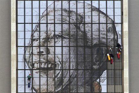 Rope access technicians work to complete a huge portrait of former South African President Nelson Mandela on the windows of the Civic Centre