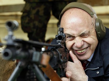 Swiss President Ueli Maurer aims at a target at 300 metres (984.25 feet) distance during a shooting exercise together with the Foreign Diplo