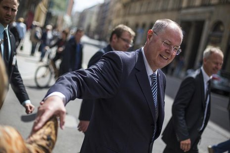 The top-candidate of the Social Democratic Party (SPD) in this year's German general election Peer Steinbrueck shakes hands with a passerby