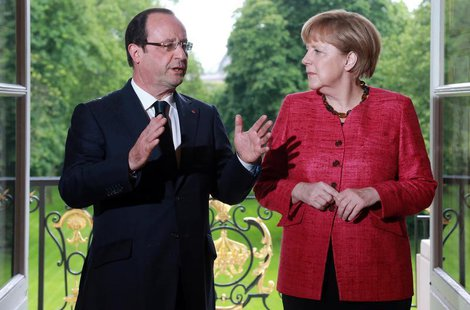 France's President Francois Hollande (L) and German Chancellor Angela Merkel arrive for a meeting at the Elysee Palace in Paris, May 30, 201