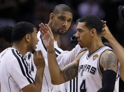 San Antonio Spurs' Danny Green (R), Tim Duncan (C) and Cory Joseph celebrate during a timeout in second quarter play against the Miami Heat