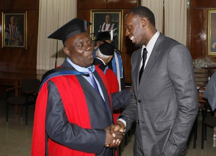 Jamaica's Olympic sprinter Usain Bolt (R) congratulates his coach Glen Mills after Mills received the degree of Doctor Honoris Causa from th