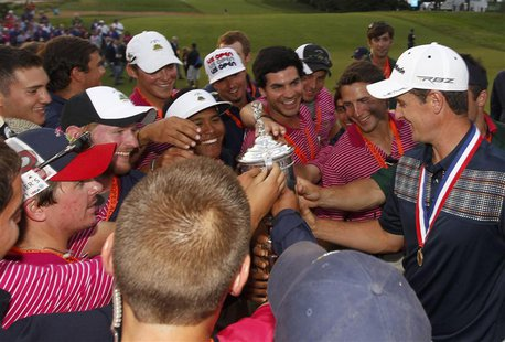England's Justin Rose (R) shows off the U.S. Open Trophy after winning the 2013 U.S. Open golf championship at the Merion Golf Club in Ardmo