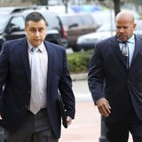 George Zimmerman is escorted by a private security guard as he arrives for a hearing in Sanford, Florida, December 11, 2012. REUTERS/Joe Bur
