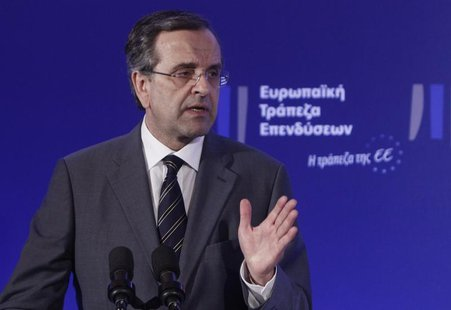 Greece's Prime Minister Antonis Samaras gestures as he delivers his speech during an agreement signing with the European Investment Bank (EI