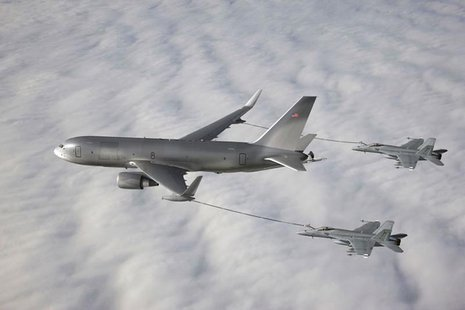 The Boeing 767-based NewGen Tanker is pictured simultaneously refueling two F/A-18 Super Hornet aircraft from the wing air refueling pods in