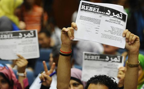 "Protesters opposing Egyptian President Mohamed Mursi hold up documents from the ""Tamarod"" campaign during a news conference at their headqua"