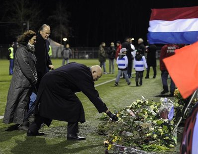 Michael van Praag, president of the Royal Dutch Football Association (KNVB), places flowers on the pitch of the soccer club Buitenboys after