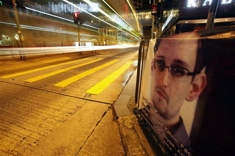 A bus passes by a poster of Edward Snowden, a former contractor at the National Security Agency (NSA), displayed by his supporters at Hong K