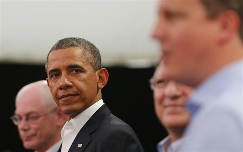 U.S. President Barack Obama glances at Britain's Prime Minister David Cameron (R) during a news conference with European Union officials at