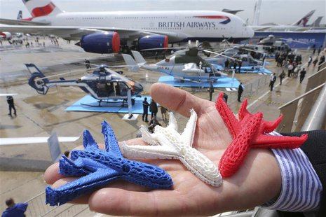 An Airbus employee presents three model airplanes in blue, white and red, made from starch using a 3D printing technique during the opening
