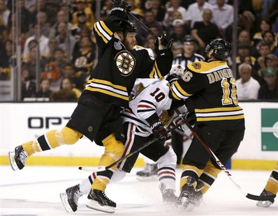Boston Bruins' Shawn Thornton (22) and Kaspars Daugavins (16) collide with Chicago Blackhawks center Patrick Sharp (10) during the first per