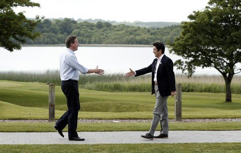 British Prime Minister David Cameron (L) welcomes Japanese Prime Minister Shinzo Abe for the first plenary session of the G8 Summit at Lough