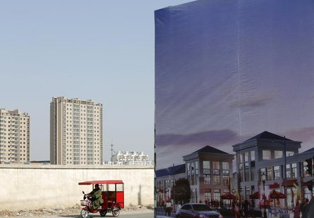 A tricycle drives past an large advertisement board of a new apartment complex at a new residential town in Beijing February 27, 2013. REUTE