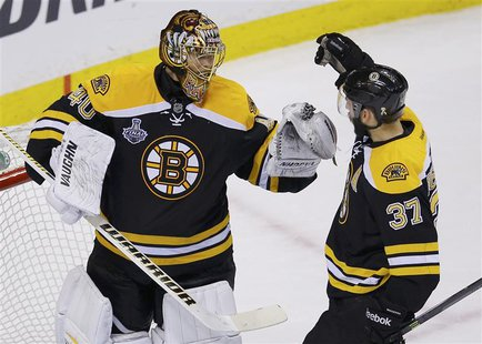 Boston Bruins' Patrice Bergeron (R) congratulates goalie Tuukka Rask after his shutout win over the Chicago Blackhawks in Game 3 of their NH
