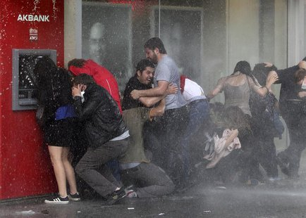 Anti-government protesters try to protect themselves from a water cannon as riot police disperse them during a protest in Ankara June 5, 201