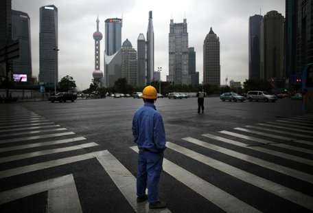 A construction worker looks at Pudong financial district as he wait to cross an avenue in Shanghai May 30, 2013. REUTERS/Carlos Barria