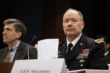 Director of the National Security Agency (NSA) U.S. Army General Keith Alexander arranges his notes as he arrives to testify before a U.S. R