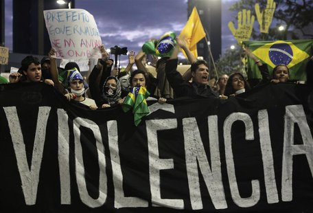 Demonstrators shout anti-government slogans behind a banner, which reads as 'violence', during one of many protests around Brazil's major ci