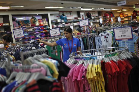A sales assistant arranges clothing inside a V-Mart retail store in New Delhi April 6, 2013. REUTERS/Adnan Abidi