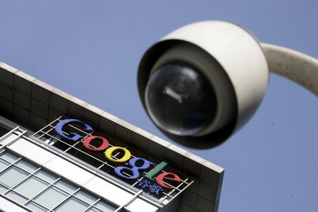 The Google logo is seen on the top of its China headquarters building behind a road surveillance camera in Beijing January 26, 2010. REUTERS