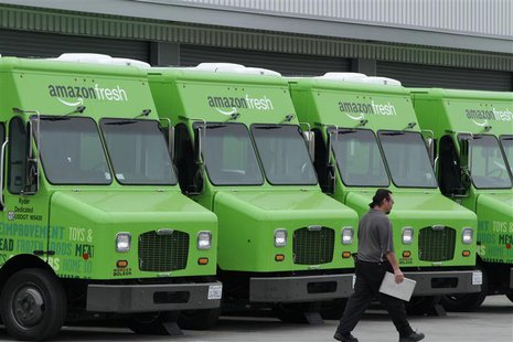 A worker walks past Amazon Fresh delivery vans parked at an Amazon Fresh warehouse in Inglewood, California, June 14, 2013. REUTERS/Jonathan