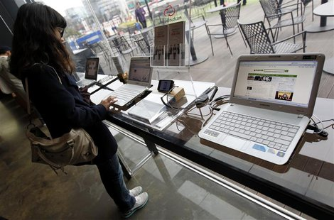A woman surfs the Internet on a computer for visitors at a registration desk at South Korean mobile carrier KT's headquarters in Seoul Decem