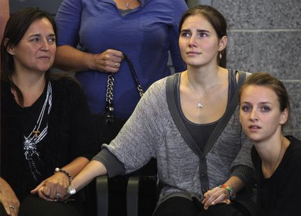Amanda Knox (C) holds hands with her mother Edda Mellas (L) and her younger sister Deanna Knox (R) at a news conference at Sea-Tac Internati