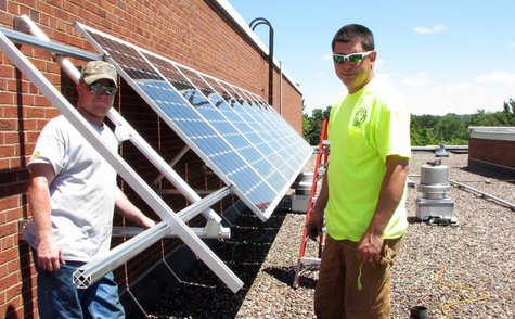 Technicians from Eland Electric install a solar panel array on the roof of Newman Catholic High School, June 18 2013