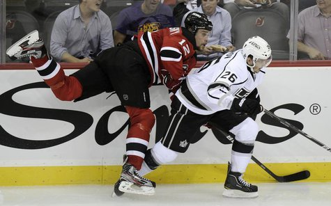 Los Angeles Kings' Slava Voynov (R) checks New Jersey Devils' Alexei Ponikarovsky during the second period in Game 1 of the NHL Stanley Cup