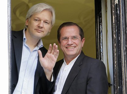 WikiLeaks founder Julian Assange waves from a window with Ecuador's Foreign Affairs Minister Ricardo Patino (R) at Ecuador's embassy in cent
