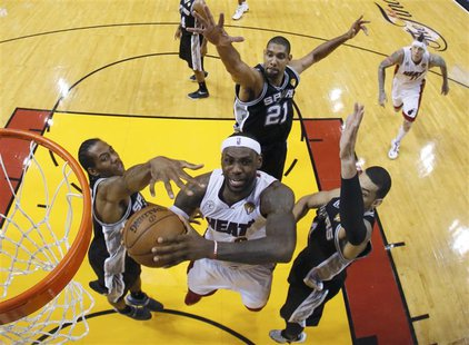 Miami Heat small forward LeBron James (6) goes to the basket past San Antonio Spurs' Tim Duncan (21), Danny Green (4) and Kawhi Leonard (2)