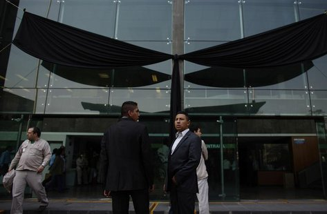 Presidential guards stand in front a black ribbon after a tribute for the victims of an explosion at the headquarters of the state oil monop