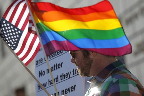 A man carries flags at a rally in support of same-sex marriage at the State of California Supreme Court in San Francisco, California March 2