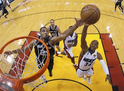 San Antonio Spurs power forward Tim Duncan (21) and Miami Heat shooting guard Ray Allen (34) reach for a rebound during Game 6 of their NBA