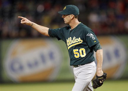 Oakland Athletics pitcher Grant Balfour points to left field after getting the last out against the Texas Rangers in the ninth inning of the