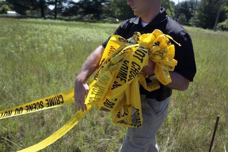 A federal investigator carries yellow crime tape at a field which investigators are prepared to dig up for the remains of former Teamsters b