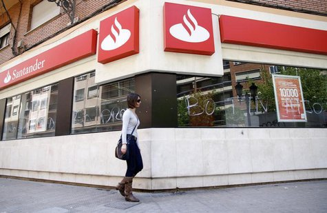 "A woman walks past the vandalized windows of a Banco Santander branch in Valencia, May 14, 2013. The words on the windows read, ""Botin"" (a r"